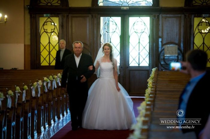 tēvs ved pie altāra kāzu ceremonijā
